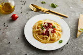 chutné boloňské těstoviny s rajčatovou omáčkou a parmezánem na bílém talíři v blízkosti ingrediencí a příborů na šedém pozadí