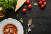 vrchní pohled na chutné boloňské těstoviny s rajčatovou omáčkou a parmezánem v bílém talíři v blízkosti ingrediencí a příborů na černém dřevěném pozadí