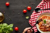 oříznutý pohled na člověka, jak jí chutné boloňské těstoviny s rajčatovou omáčkou a parmezánem z bílého talíře na černém dřevěném stole se ingrediencemi a kontroluje ubrousek