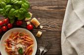 Fényképek felső kilátás ízletes bolognai tészta paradicsom mártással és parmezán fehér lemez közelében összetevők és evőeszközök fa asztalon