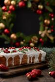 selektiver Schwerpunkt traditioneller Weihnachtskuchen mit Preiselbeeren in der Nähe von Weihnachtskranz mit Kugeln auf Holztisch isoliert auf schwarz