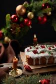 hagyományos karácsonyi torta áfonyával közel karácsonyi koszorú baubles és gyertyák fa asztalon elszigetelt fekete