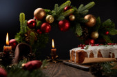 hagyományos karácsonyi torta áfonyával közel karácsonyi koszorú baubles és égő gyertyák fa asztal elszigetelt fekete