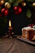 selektiver Schwerpunkt traditioneller Weihnachtskuchen mit Preiselbeeren in der Nähe von Weihnachtskranz mit Kugeln und brennender Kerze auf Holztisch isoliert auf schwarz