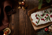 top view of traditional Christmas cake with cranberry near pine with baubles and candles on wooden table