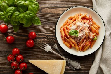 Top view of tasty bolognese pasta with tomato sauce and Parmesan in white plate near ingredients and cutlery on wooden table stock vector