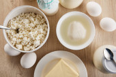top view of fresh organic dairy products and eggs on wooden table
