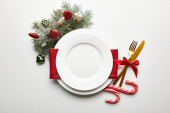 top view of festive Christmas table setting on white background with decoration, pine branch and candies
