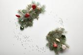 vrchní pohled na slavnostní vánoční zdobené borové větve s ozdoby a konfety na bílém pozadí