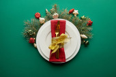 top view of white plate with napkin, cutlery near festive Christmas tree branch with baubles on green background