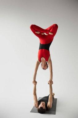European couple practicing acroyoga on yoga mat isolated on grey stock vector