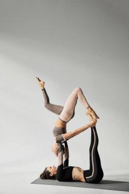 Young women practicing acroyoga on yoga mat in studio