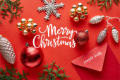 top view of shiny Christmas decoration, envelope and thuja on red background with Merry Christmas illustration