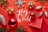 horní pohled na lesklé vánoční dekorace, obálky a thuja na červeném pozadí s radostí do světa ilustrace