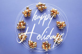 round frame of shiny golden Christmas decoration on blue background with Happy holidays lettering
