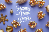 top view of shiny golden Christmas decoration on blue background with happy new year lettering