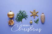 top view of shiny golden Christmas decoration, green thuja branches on blue background with Merry Christmas illustration