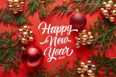 horní pohled na lesklé vánoční dekorace a thuja na červeném pozadí s šťastný nový rok nápisy