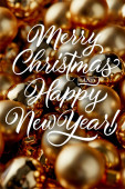 close up view of shiny golden Christmas baubles with merry Christmas and happy New year illustration