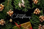 vrchní pohled na lesklé zlaté vánoční dekorace, zelené thuja větve a dárkové krabice izolované na černé s veselou vánoční ilustrací
