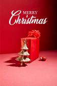červená dárková krabice a dekorativní zlatý vánoční stromek s cetkou na červeném pozadí s veselou vánoční ilustrací