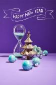 selektiver Schwerpunkt der dekorativen Weihnachten in der Nähe von blauen Christbaumkugeln und Sanduhr auf lila Hintergrund mit frohem neuen Jahr Schriftzug