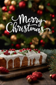 Fotografie selective focus of traditional Christmas cake with cranberry near Christmas wreath with baubles on wooden table with Merry Christmas illustration