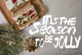 felső kilátás a hagyományos karácsonyi torta áfonya közelében baubles és fenyő fehér asztal vele az évszakban, hogy vidám betű