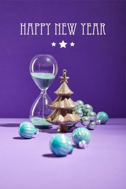 Selective focus of decorative Christmas near blue baubles and hourglass on purple background with happy new year lettering stock vector