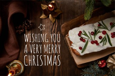 top view of traditional Christmas cake with cranberry near pine with baubles and candles on wooden table with wishing you a very Merry Christmas illustration