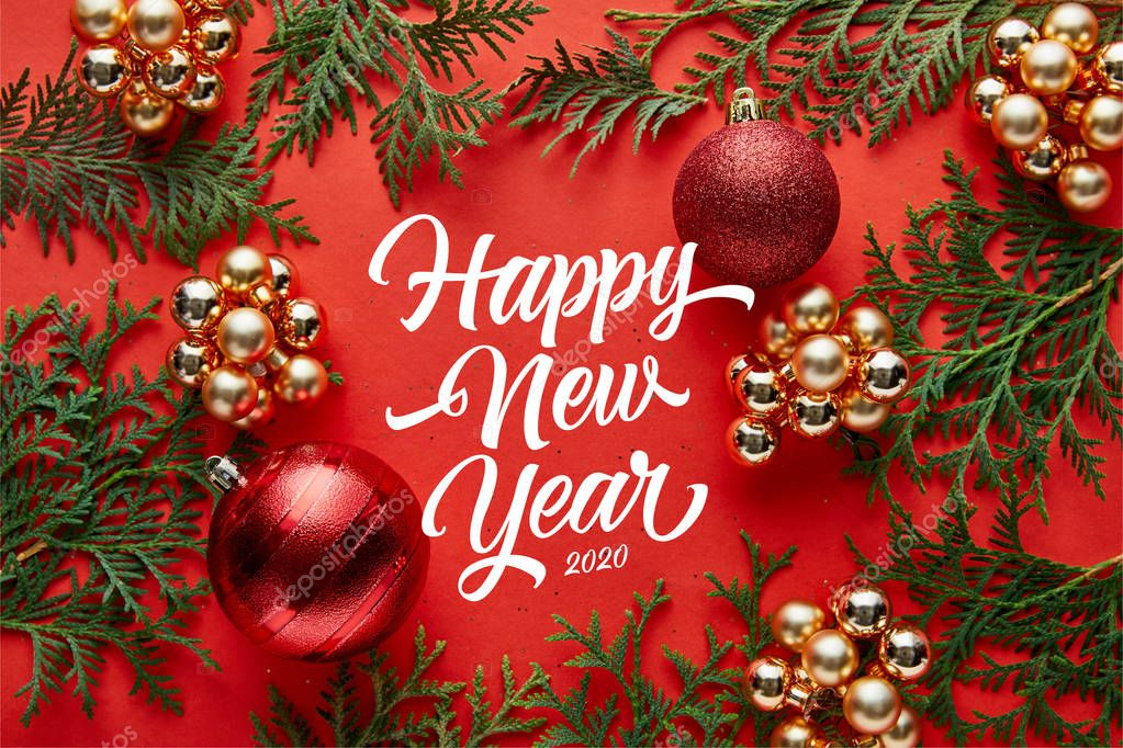 top view of shiny Christmas decoration and thuja on red background with happy new year lettering