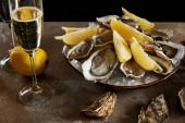 bicchieri di champagne con spumante vicino ostriche e limoni freschi in ciotola