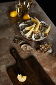 champagne glasses with sparkling wine near bottle, oysters and lemons in bowl