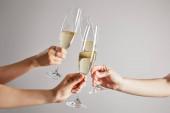 oříznutý pohled na ženy připíjející sklenice šampaňského se šumivým vínem izolovaným na šedi