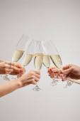 oříznutý pohled na ženy a muže připíjející sklenice šampaňského se šumivým vínem izolovaným na šedi