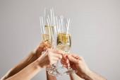 abgeschnittene Ansicht von Männern und Frauen, die Champagnergläser mit frischem Sekt isoliert auf Grau anstoßen
