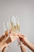 oříznutý pohled na ženy a muže, jak připíjejí, zatímco drží sklenice šampaňského se šumivým vínem izolovaným na šedi