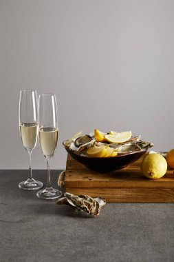 delicious oysters and lemons in bowl near champagne glasses with sparkling wine isolated on grey