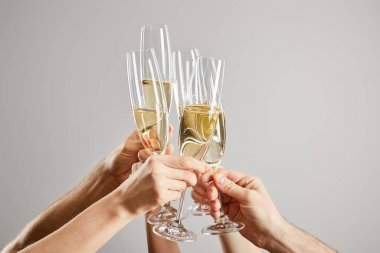 Cropped view of men and women toasting champagne glasses with fresh sparkling wine isolated on grey stock vector