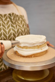 Cropped view of confectioner with pastry bag adding cream on biscuit on stand isolated on grey