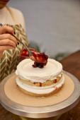 Oříznutý pohled na cukráře s lžící, jak dává jahodovou marmeládu na dort se smetanou
