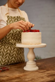 Cropped view of smiling confectioner decorating cake with sweet redcurrant