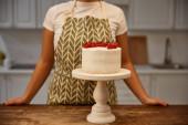 Oříznutý pohled na cukráře stojící vedle chutného dortu s červeným rybízem na stole