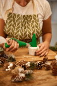 Cropped view of confectioner decorating Christmas tree cupcake with sweet cream beside pine cones on table