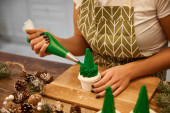 Cropped view of confectioner adding tasty cream on Christmas tree cupcakes with spruce cones on wooden table