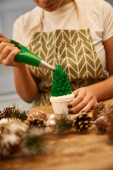 Cropped view of confectioner pouring sweet green cream on Christmas tree cupcake beside spruce cones on table