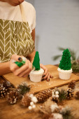 Cropped view of confectioner using pastry bag with cream on Christmas tree cupcakes beside spruce cones on table