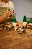 Cropped view of confectioner decorating Christmas tree cupcakes with green sweet cream beside spruce cones on table