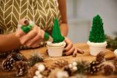 Fotografie Selektivní zaměření cukráře pracujícího s dortíky na vánoční stromeček vedle smrkových kuželů na stole, oříznutý pohled