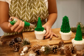 Cropped view of confectioner making Christmas tree cupcakes with green sweet cream beside spruce cones on table